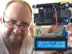 "Photo of a man with a homemade clock showing a digital readout saying ""2015-09-17 20:47 #IStandWithAhmed"""