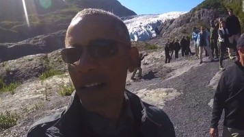 Barack Obama, wearing sunglasses, takes a selfie in front of a glacier in Alaska. Group of people in the background.